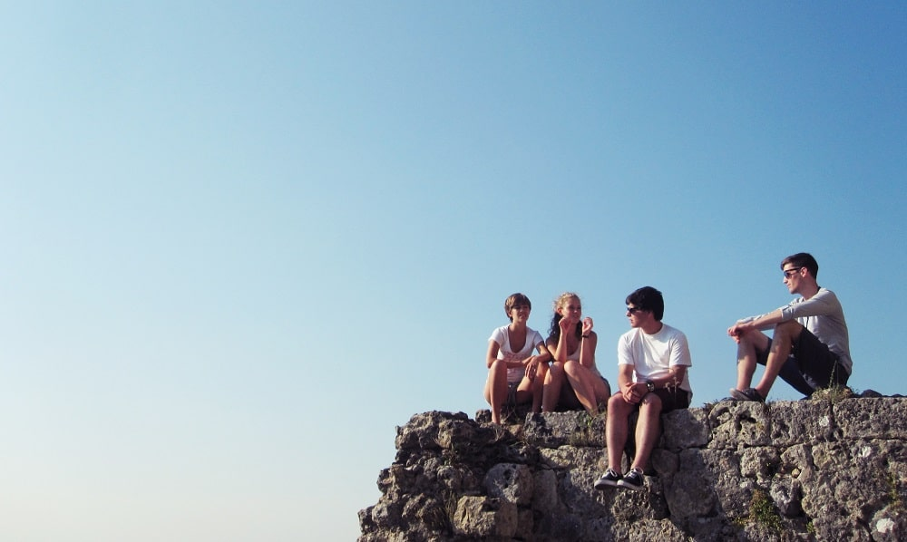 Teens on rock outcrop discuss good money habits for kids