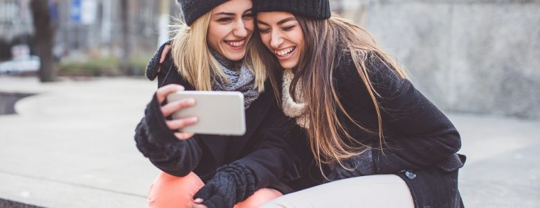 Two young women on bench look at best financial apps for teens and young adults on an iPhone