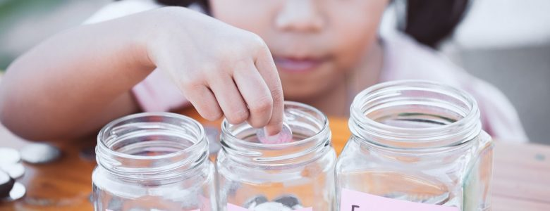 Little girl with three jars of money applies saving and spending milestones for kids by age to her saving method