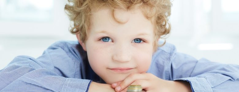 Little boy with piles of coins needs to know savings account options for kids