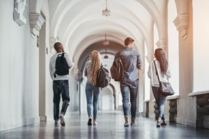 Four students in college finances, walking towards future, secure in their college finances and beyond